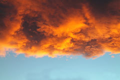 Orange and Gold Cloud at Sunset. Against a Blue Sky Royalty Free Stock Photos
