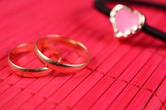 Orange gold-plated heart with two wedding rings Stock Images