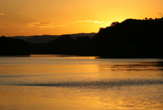Orange gold sunset sky over water. Glorious colourful orange gold sunset over hills and water Stock Photo
