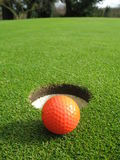 Orange golf ball. On the green beside the hole Stock Image