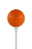 Orange golf ball. Isolated orange golf ball on a white tee Royalty Free Stock Image