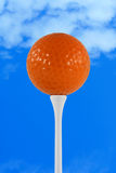 Orange golf ball against blue sky Stock Photos