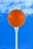 Orange golf ball against blue sky. A Orange golf ball against blue sky Stock Photos