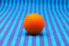 Orange golf ball on blue striped table. Orange golf ball on blue striped tablecloth Stock Photography