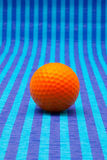 Orange golf ball on blue striped table. Orange golf ball on blue striped tablecloth Stock Image