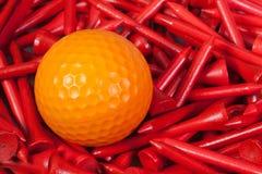 Orange golf ball lying between wooden tees. Orange  golf ball lying between red wooden golf tees Royalty Free Stock Image