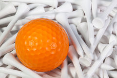 Orange golf ball lying between wooden tees. Orange golf ball lying between white wooden golf tees Royalty Free Stock Images