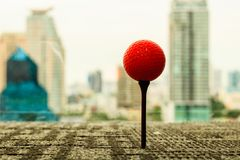 Orange golf ball on tee behind cityscape scene in the office. Go royalty free stock image
