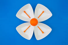 Orange golf ball on the triangular ceramic bowls. For sushi on the blue wooden table Royalty Free Stock Photo