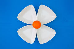 Orange golf ball on the triangular ceramic bowls. For sushi on the blue wooden table Royalty Free Stock Images