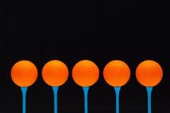 Orange golf balls on blue wooden tees. Golf balls on blue wooden tees Stock Images