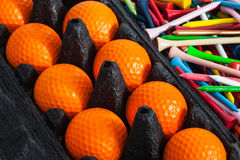 Orange golf balls and tees. The orange golf ball and different colorful tees Royalty Free Stock Image