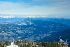 Orange gondola cabins of cableway lift on winter snowy mountains background beautiful scenery royalty free stock image