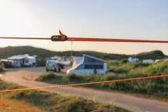 Orange grabbrep och svartregulator som rymmer ett tält stadigt i dess ställe royaltyfri bild