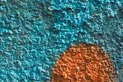 Orange graffiti detail on a blue painted wall, facade. Abstract background, wallpaper. Exterior wall stock photos