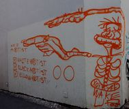 Painted Graffiti On White Wall In Faro Portugal. Orange graffiti of a person along with written explanation painted on a white wall in Faro Portugal royalty free stock photo