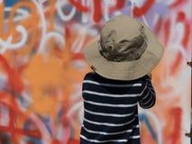 Orange Graffitiwand des Jungensommerhutes stockbilder
