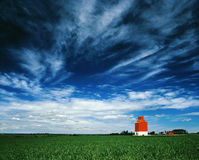 Orange grain elevator against a big blue sky. A lone grain elevator sits on the Canadian prairies with a big blue sky overhead. A field of wheat grows in the Stock Images