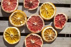 Orange and grape fruit slices dried. Dry orange and grape fruit slices, on wooden background Royalty Free Stock Image