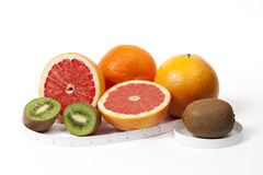 Orange, grapefruit, kiwi and tipe measure in inches over white Royalty Free Stock Photography