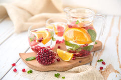 Orange Grapefruit Pomegranate and Mint Detox Water. On wooden table Stock Photo