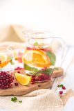 Orange Grapefruit Pomegranate and Mint Detox Water. On wooden table Stock Photos