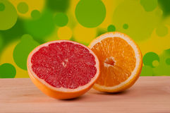 Orange and grapefruit slices on a wooden board with mottled yellow-green background Stock Image