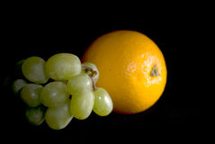 Orange and Grapes. A view of fresh grapes and an orange, isolated on a black studio background Stock Photography