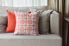 Orange and gray pillows on gray sofa Royalty Free Stock Image