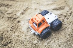 Orange and Gray Plastic Truck Toy on Sand Royalty Free Stock Photos