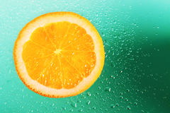Orange on green background. With water droplets Stock Photo