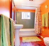 Orange and green bathroom with tub and wood floor. Stock Photo