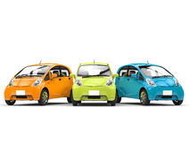 Orange, green and blue small ecomonic electric cars side by side Stock Image