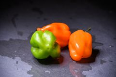 Bright colourful green and orange habanero hot peppers on table Royalty Free Stock Photo