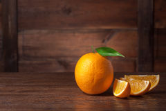 Orange with green leaf and slices on wood Stock Photos