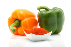 Orange and green peppers and paprika in a dish isolated on white background Royalty Free Stock Photo