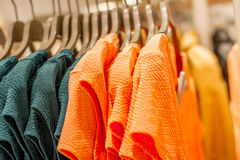 Orange and green shirts on hangers in shop Stock Image