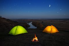 Orange and green tent by the river at night royalty free stock images