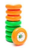 Orange and green wheels isolated over white. Orange and green inline rollerskates wheels isolated over white Stock Images