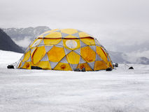 Orange and grey tent on the glacier. Royalty Free Stock Photography