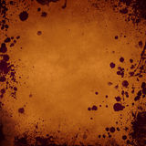 Orange grunge background with splatters in the borders Stock Photography