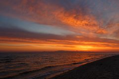 Orange gryning för vår på kusten av det lugna havet under tidvattnet Royaltyfri Foto
