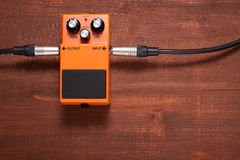 Orange guitar pedal. On the wooden table Royalty Free Stock Photography