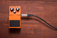 Orange guitar pedal. On the wooden table Stock Photography