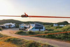 Orange guy rope and black adjuster holding a tent steady in its place. Firm fixation with caravans, campers and camping pitches in the background. Sun is royalty free stock image
