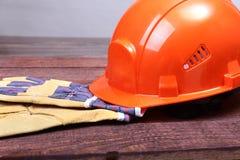 Orange hård hatt och handskar för arbete på wood bakgrund Royaltyfri Fotografi