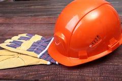 Orange hård hatt och handskar för arbete på wood bakgrund Fotografering för Bildbyråer