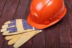 Orange hård hatt och handskar för arbete på wood bakgrund Arkivbild