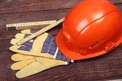 Orange hård hatt och handskar för arbete på wood bakgrund Arkivfoton