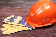 Orange hård hatt och handskar för arbete på wood bakgrund Royaltyfri Foto